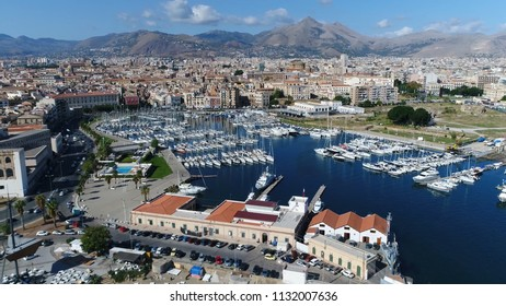 Aerial bird view photo of marina yacht club located at Palermo Sicily Italy showing streets on left and harbor on right furthermore showing the city center and mountains in background