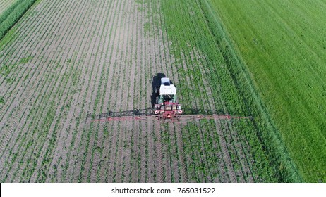 Aerial bird view photo of tractor spraying chemicals over young corn field mostly glyphosate is used as pre-harvest herbicide and harvest aid on crops and is used to kill weeds