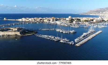 Aerial bird view photo of Trapani marina showing several sailing boats in the recreational harbor and in background showing Trapani city located in Sicily Italy beautiful summer evening