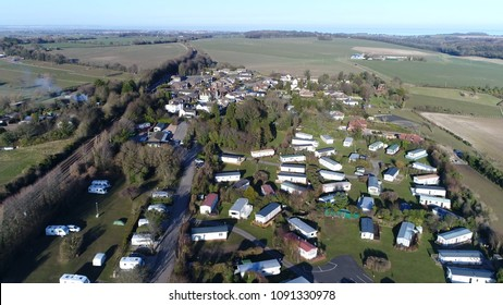 Aerial bird view picture of Farm Campsite and Holiday Park showing the long-term campsite that includes permanent and semi-permanent setups also showing caravans below