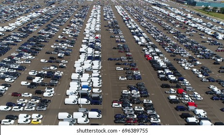 Aerial bird-eye photo above car distribution center storage facility at harbor showing cars and delivered vans deliverd from ships ready to be delivered to car dealerships automotive industry scene