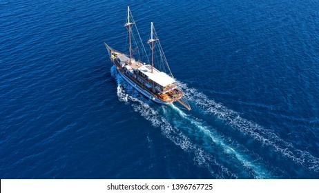 Aerial birds eye drone view of beautiful wooden sailboat in deep blue sea of island of Mykonos, Cyclades, Greece