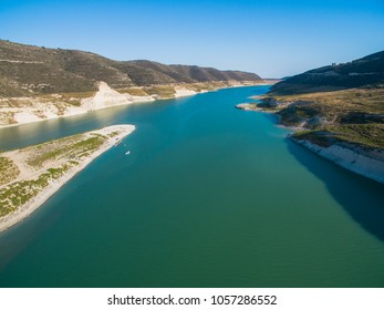 Aerial Bird's eye view of artificial lake at the largest dam in Cyprus, Kouris reservoir, Limassol. View of the river split peninsula, earthfill embankment and hills around water from above.