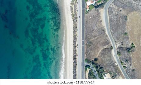 Aerial, birds eye, view of beach-highway-mountains in California.