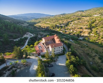 Aerial bird's eye view of christian greek orthodox Holy Monastery of Panayia Amasgous in Monagri village,Limassol,Cyprus. The traditional stone ceramic roof tiled church in the forest slope from above