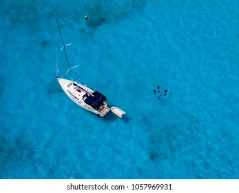 Aerial birds eye view from drone of sailboat in turquoise water, island, Praslin island Seychelles Indian ocean, people snorkling