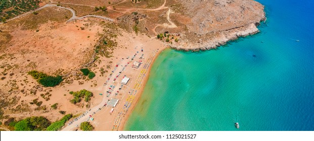 Aerial birds eye view drone photo Agia Agathi beach near Feraklos castle on Rhodes island, Dodecanese, Greece. Panorama with sand beach and clear blue water. Famous tourist destination in South Europe