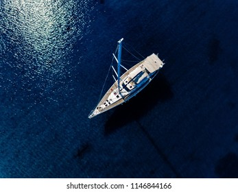 Aerial birds eye view from drone of yacht in deep blue sea in Greece.