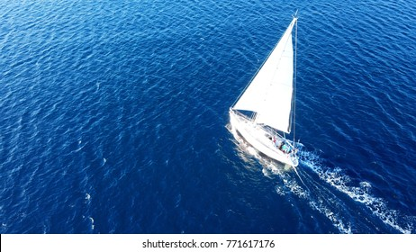 Aerial birds eye view from drone of sailboat in turquoise water, island of Mykonos, Cyclades, Greece