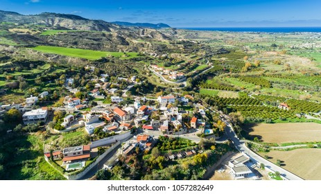 Aerial bird's eye view of Goudi village in Polis Chrysochous valley, Paphos, Cyprus. View of traditional ceramic tile roof houses, church, trees, hills and Akamas - Latchi beach bay from above.