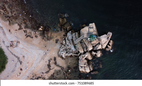 Aerial Bird's eye view of the green Lighthouse based on big rocks at the coastline and beachfront of Lei Yue Mun