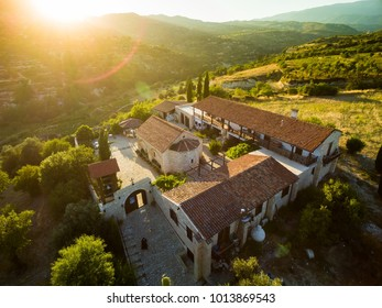 Aerial bird's eye view of Holy monastery of Archangel Michael (Archangelou Michail) in Monagri village, Limassol, Cyprus, an ancient christian religious monument, at sunset flare, from above.