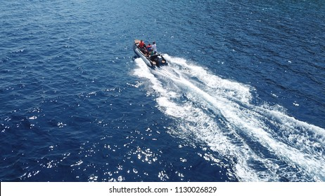 Aerial bird's eye view of inflatable rib boat cruising in high speed in deep blue mediterranean sea