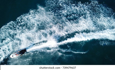 Aerial bird's eye view of jet ski cruising in high speed in turquoise clear water sea