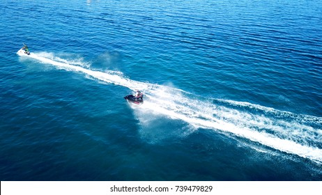 Aerial bird's eye view of jet skis racing in high speed competition in turquoise clear water sea