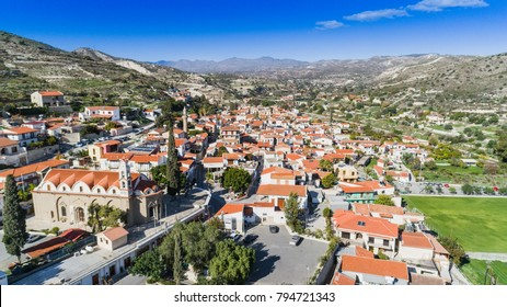 Aerial bird's eye view of Kalavasos village valley, Larnaca, Cyprus. A traditional town with ceramic roof tiles houses, a greek orthodox christian church and muslim mosque around hills from above.