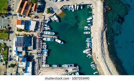 Aerial bird's eye view of Latchi port, Akamas peninsula, Polis Chrysochous, Paphos, Cyprus. The Latsi harbour with boats and yachts aligned, fish restaurants, promenade, beach tourist area from above.