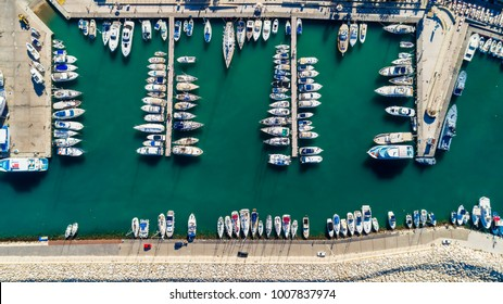 Aerial bird's eye view of Latchi port, Akamas peninsula, Polis Chrysochous, Paphos, Cyprus. The Latsi harbour with boats and yachts aligned, fish restaurants, promenade, beach tourist area from above