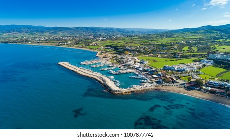 Aerial bird's eye view of Latchi port, Akamas peninsula, Polis Chrysochous, Paphos,Cyprus. Latsi harbour with boats and yachts, fish restaurant, promenade, beach tourist area and mountains from above