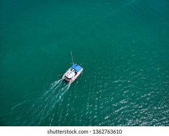 Aerial bird's eye view of modern boat cruising in high speed in deep blue Andaman sea. Phuket. Thailand.