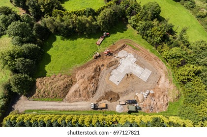 Aerial birds eye view of a new build concrete foundation for a home in the countryside. Green field with machinery digger and dumper truck and tractor.