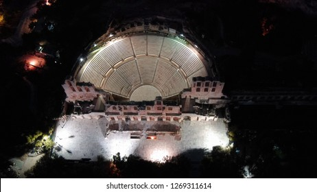 Aerial birds eye view night shot taken by drone of iconic Odeon or Amphitheater of Herodes Atticus in the slopes of Acropolis hill, Athens historic centre, Attica, Greece
