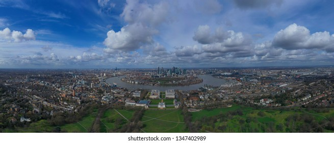 Aerial bird's eye view panoramic drone photo of Greenwich park with views to Canary Wharf and University of Greenwich with beautiful cloudy sky, Isle of Dogs, London, United Kingdom