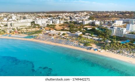 Aerial bird's eye view of Pantachou - Limanaki beach (Kaliva), Ayia Napa, Famagusta, Cyprus. The landmark tourist attraction bay with golden sand, sunbeds,sea bar restaurants in Agia Napa from above. - Shutterstock ID 1749442271
