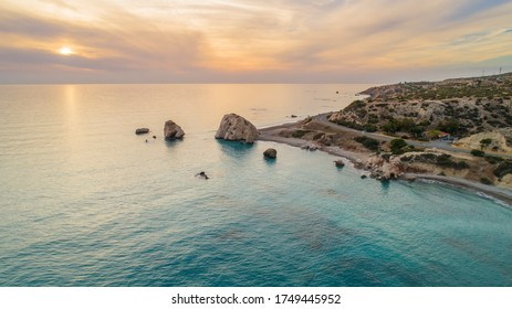 Aerial Bird's eye view of Petra tou Romiou, aka Aphrodite's rock a famous tourist travel destination landmark in Paphos, Cyprus. The sea bay of goddess Afroditi birthplace at sunset from above.