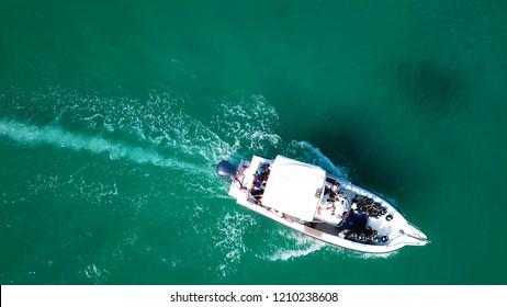 Aerial bird's eye view photo taken by drone of boat cruising in caribbean tropical beach with emerald clear sea