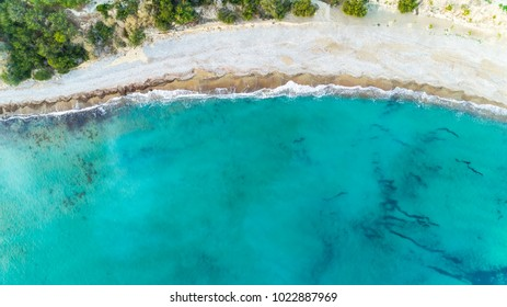 Aerial bird's eye view of Pissouri bay, a village settlement between Limassol and Paphos in Cyprus. The shore, beach with white sand pebbles and crystal clear clean blue water on the shore from above.