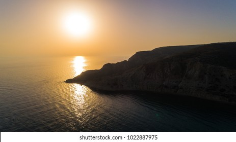 Aerial bird's eye view of Pissouri bay, a village settlement between Limassol and Paphos in Cyprus. Silthouette of the coast, beach, hills over the sea at sunset from above.