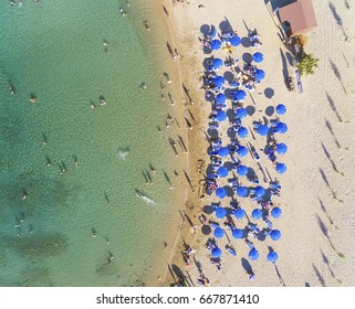 Aerial bird's eye view of sandy beach in Protaras, Famagusta, Cyprus island at Ayia Triada bay. Sun umbrellas, sea beds and silhouette of people sunbathing and swimming during the summer holiday heat