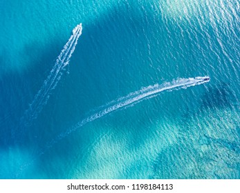 Aerial bird's eye view of two boats cruising in clear turquoise sea water.