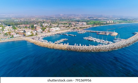 Aerial bird's eye view of Zygi fishing village port, Larnaca, Cyprus. The fish boats moored in the harbour with docked yachts and skyline of the town near Limassol city from above.