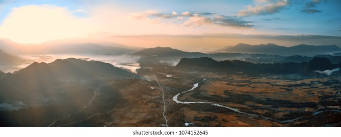 Aerial bird's-eye sunrise time view on valley landscape with karst mountains, small town, river and rice fields. Laos, Vang Vieng.