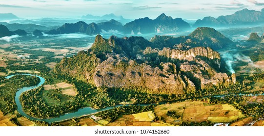 Aerial bird's-eye sunrise time view on valley landscape with karst mountains, river and rice fields. Laos, Vang Vieng.