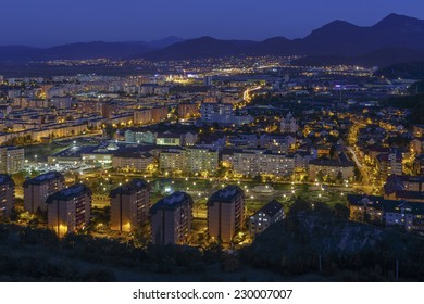 Aerial blue hour cityscape of downtown residential district of Brasov city, Romania, surrounded by Carpathians mountains range.