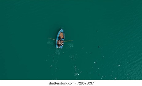 Aerial Boat on the lake. Aerial view on two men in a boat on a lake, rowed to the shore. Lonely boat in the middle of the river, lake. Boat single row on sea with reflection in the water in the