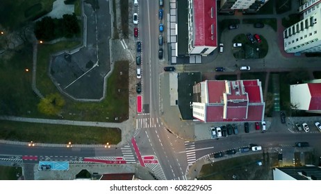 Aerial camera following biker in blue riding his cycle along bicycle paths, top view. Modern urban residential area