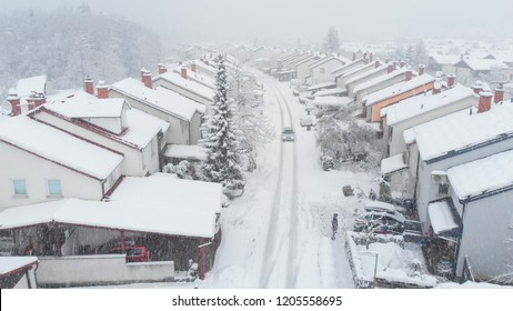 AERIAL: Car drives down the snowy road leading through the suburban neighborhood and past the kids enjoying the winter weather. Flying above snow covered road running past people's homes in suburbia