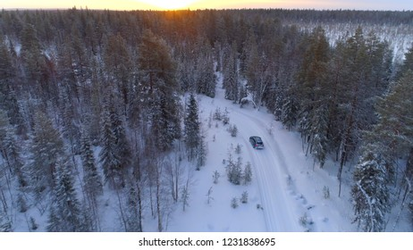 AERIAL Car driving through slippery bend on snowy road in wintry forest, Lapland