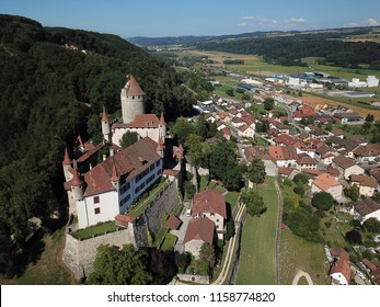 Aerial of Chateau de Lucens looming over the small town bearing the same name in Canton de Vaud, Switzerland.