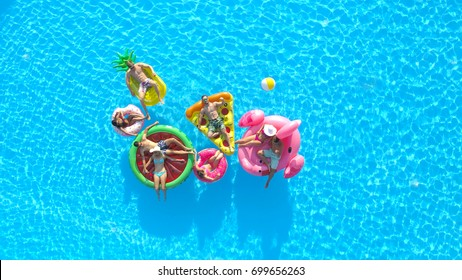 AERIAL: Cheerful fit people on summer vacation enjoying on fun inflatable floats