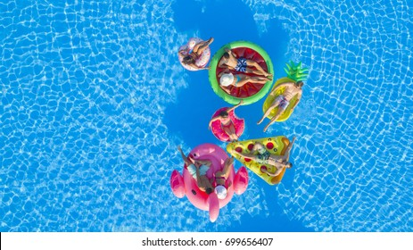 AERIAL: Cheerful teenage friends playing volleyball on fun floaties in pool