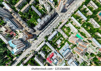 Aerial city view with crossroads and roads, houses, buildings, parks and parking lots, bridges. Helicopter drone shot. Wide Panoramic image.