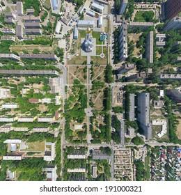Aerial city view with crossroads, roads, houses, buildings, parks, parking lots, bridges