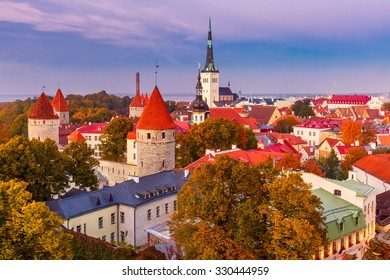 Aerial cityscape with Medieval Old Town, St. Olaf Baptist Church and Tallinn City Wall illuminated in autumn twilight, Tallinn, Estonia