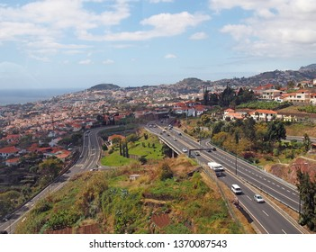 an aerial cityscape view of funchal showing traffic on the main VR1 motorway running into the city with the coast visible in the distance