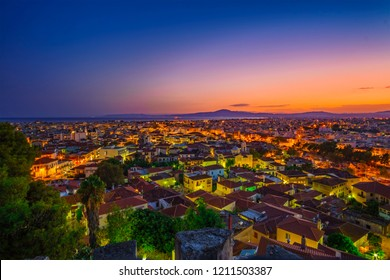 Aerial cityscape view of the wonderful old town of Kalamata City illuminated at night. Photo taken during the blue hour from the old Castle at Sunset. Messenia, Greece